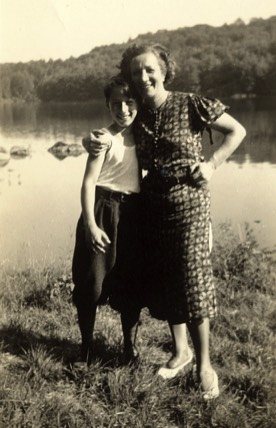black and white vintage photo of mother and son standing by a lake