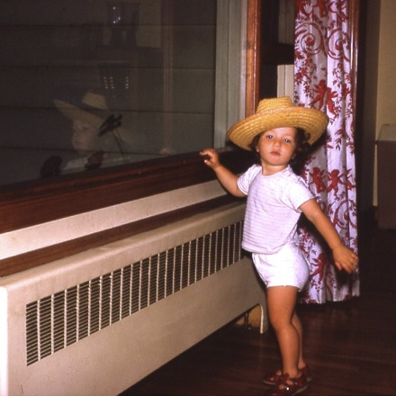 adorable young girl in straw hat by a window